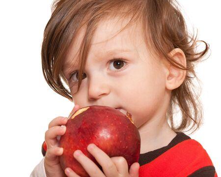 bambini pensierosi: Vicino un ritratto di un bambino bello detiene una grande mela rossa in bocca; isolato su sfondo bianco