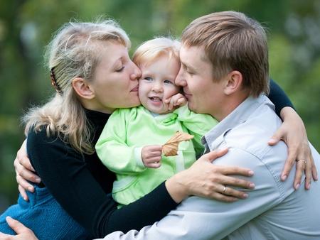 Una familia de tres fuera; pap� y mam� besando a su hija Foto de archivo - 8580129