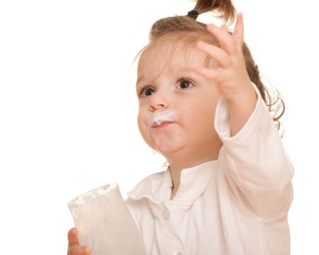 A cute toddler with milk moustache in a white shirt is holding a glass of milk; isolated on the white background photo