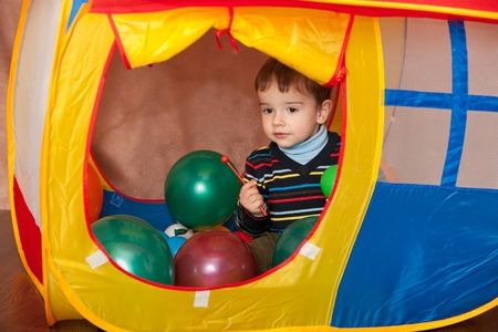 A cheerful little boy is playing in a yellow toy house photo