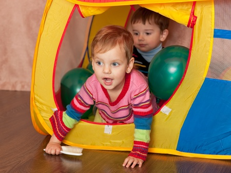 Two toddlers are playing inside a yellow toy house photo