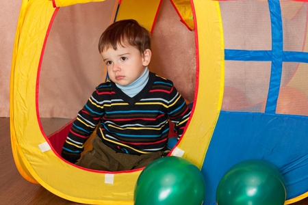A thoughtful little boy is sitting in a yellow toy house photo