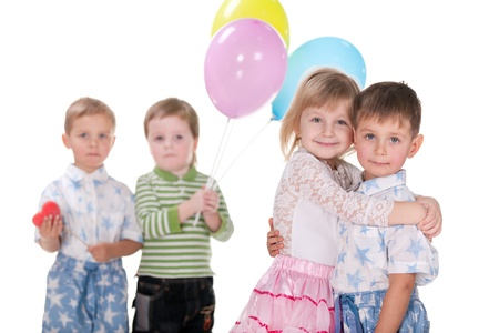 A cheerful laughing girl cuddles a little boy; his two friends are holding a red heart and vivid baloons; isolated on the white background photo