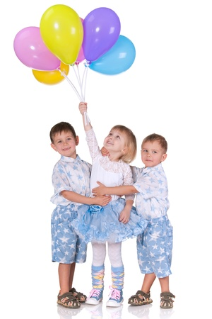 Two cheerful little boys cuddle a little pretty girl holding a pile of ballons; isolated on the white background photo