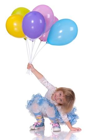 juguetes: Un niño de risa alegre en azul está jugando con globos; aislado en el fondo blanco