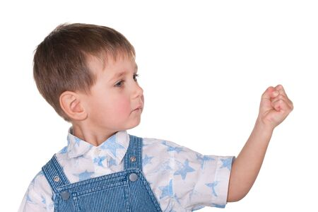 A serious little boy demonstrates how strong he is; isolated on the white background photo