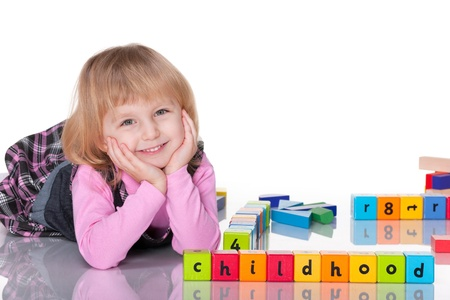block letters: A cheerful laughing kid in pink is playing with blocks; isolated on the white background