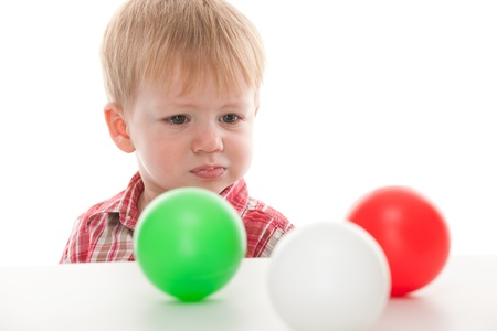 unsatisfied: An unsatisfied kid is looking at three toy balls lying on the table; isolated on the white background