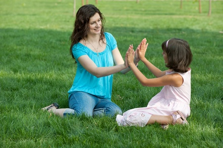 Mom amd her daughter are happy to be together outside in the summer park photo