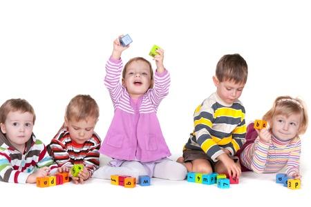 kinder: Cinco ni�os est�n jugando v�vidas bloques con letras; aislado en el fondo blanco Foto de archivo