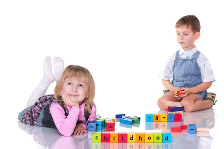 A cheerful laughing girl flirts with a little concentrated boy while playing blocks; isolated on the white background photo