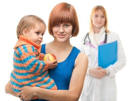 A pretty mother is holding her daughter with an apple in front of a doctor figure; isolated on the white background photo