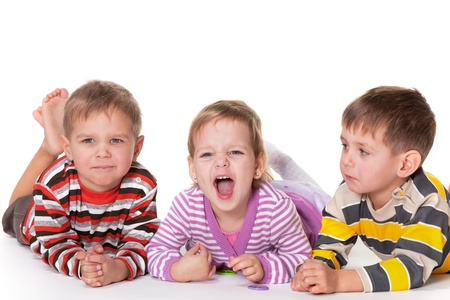Two little twins are surprised why their girl friend is shouting; isolated on the white background photo