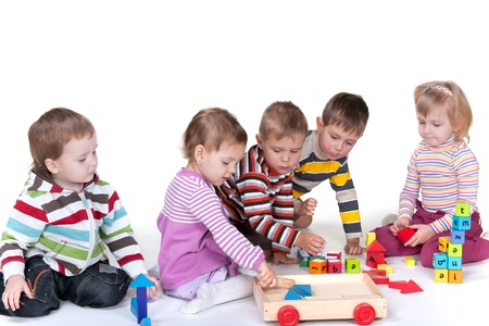A group of five kids are playing colorful toys; isolated on the white background photo