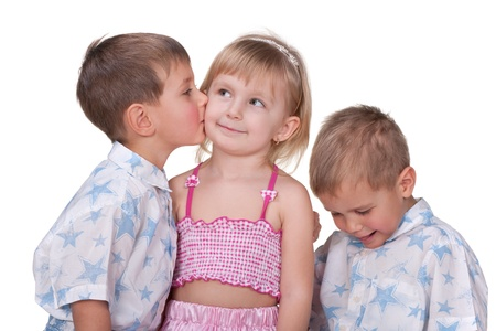 Two little twins are flirting with a little girl; isolated on the white background photo