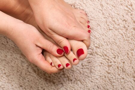 Close up hands massaging a foot at the white carpet background Stock Photo - 8902033