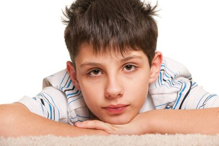 straggly: A handsome sly kid with straggly hair is lying on the white carpet; isolated on the white background