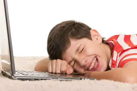 A handsome lying on the white carpet boy is crying with joy after computer game; isolated on the white background Stock Photo - 8901995