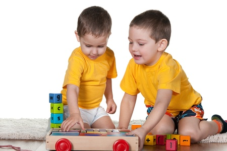 Two sitting on the carpet children in yellow are playing blocks; isolated on the white background Stock Photo - 8902018
