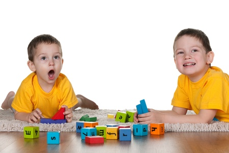 Two sitting on the carpet children in yellow are playing blocks; isolated on the white background photo