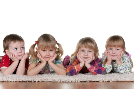 preschool kids: A little boy is lying at three smiling girls; isolated on the white background