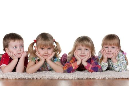 kinder: Un ni�o est� mintiendo a tres ni�as sonrientes; aislado en el fondo blanco