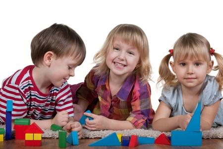 ni�os rubios: Tres acostado de los ni�os de alfombra est�n jugando bloques; aislado en el fondo blanco Foto de archivo