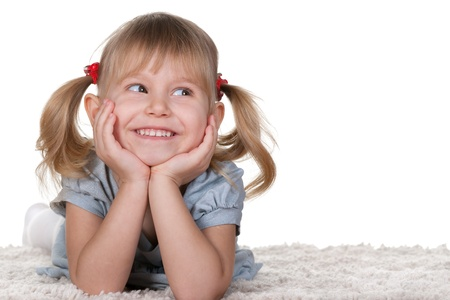 smiles teeth: A cheerful little girl with funny tails is lying on the white carpet; isolated on the white background Stock Photo