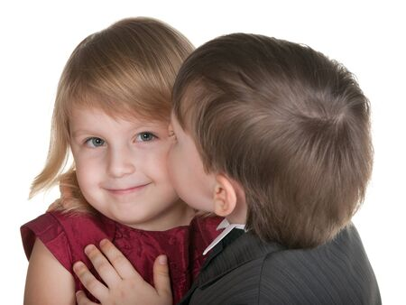 A little boy is kissing a pretty blonde girl; isolated on the white background photo