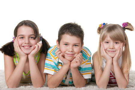 Three smiling lying on the carpet children; isolated on the white background photo
