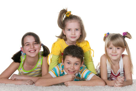 Four smiling lying on the carpet children; isolated on the white background photo