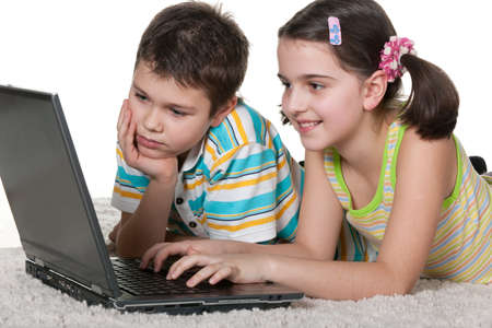 A boy and a girl are studying using a laptop; isolated on the white background photo