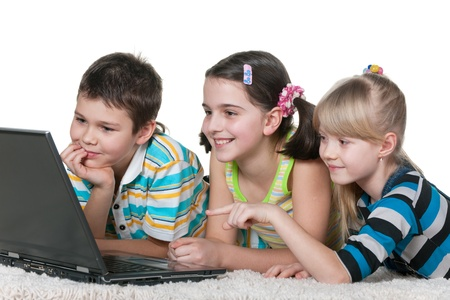 A boy and two girls are studying using a laptop; isolated on the white background photo