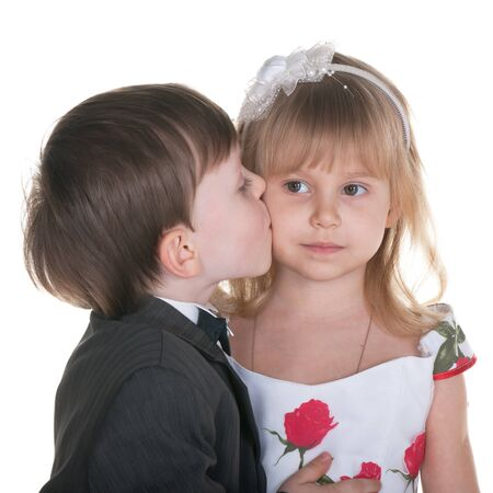 A little boy in suit kisses a little girl in a charming dress; isolated on the white background photo