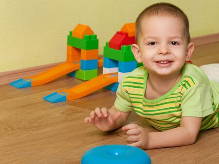 A portrait of a cheerful little kid lying on the wooden floor at the toy car track Stock Photo - 8902049