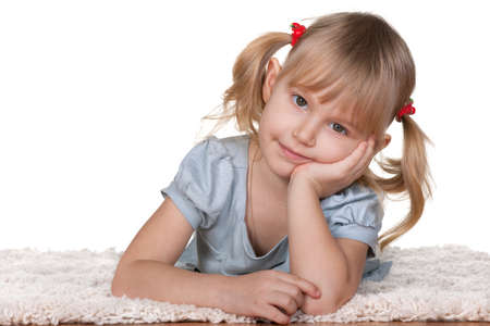 A pretty thoughtful little girl is lying on the thick carpet; isolated on the white background