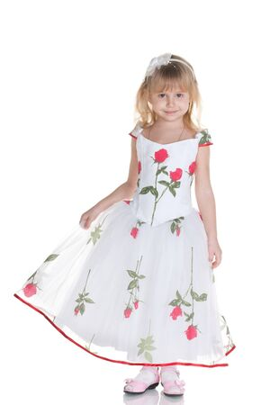 full height: A cheerful little girl is standing full height dressed in a ball gown; isolated on the white background