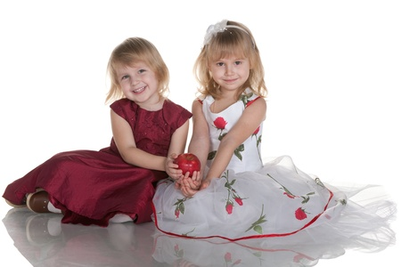 blonde little girl: Two cheerful girls in ball dresses are holding a red apple together; isolated on the white background