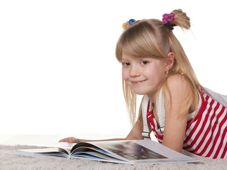 A cheerful girl is reading a book lying on the thick carpet; isolated on the white background photo