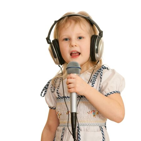 A cheerful little girl in headphones holding a microphone is singing a song; isolated on the white background photo