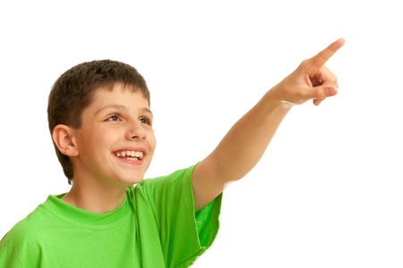 A cheerful boy in casual green shirt is showing something above; isolated on the white background Imagens