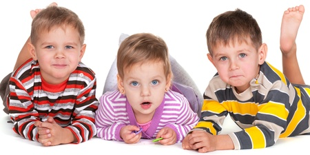 A group of three little lying children; isolated on the white background photo
