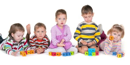A group of five kids with different emotions are playing colorful blocks; isolated on the white background photo