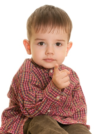 A closeup portrait of a cheerful little boy showing direction forward with his finger; isolated on the white background Stock Photo - 9015359