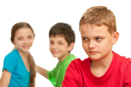 A boring kid is sitting against his happy friends; isolated on the white background photo