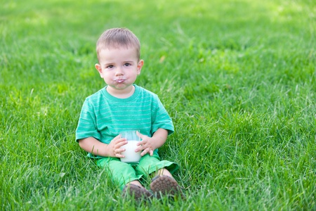 A cheerful kid is sitting on the green grass having his mouth full with milk photo
