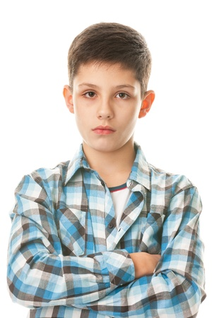 A portrait of a serious kid dressed in the checked shirt with his hands crossed; isolated on the white background photo