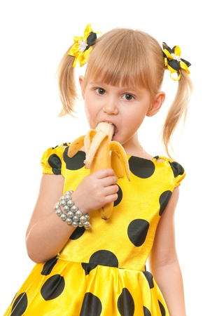 preschoolers: A portrait of a girl in yellow polka dot dress eating banana; isolated on the white background Stock Photo