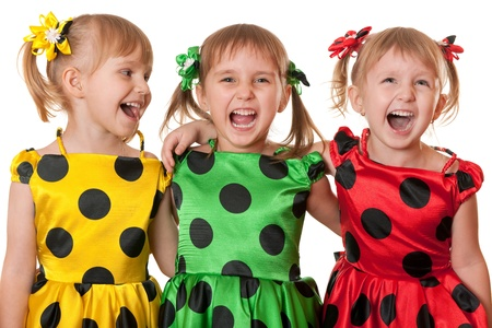 Three little girls in yellow, green and red polka dot dresses are laughing; isolated on the white background Stock Photo - 9133020
