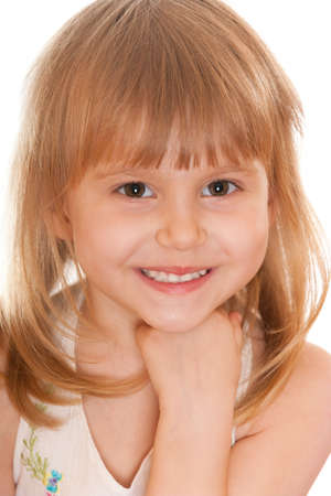 A cheerful little girl in casual is holding her head on the hand; isolated on the white background photo